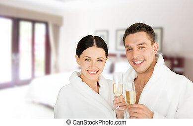 happy couple in bathrobes over spa hotel room - people,...