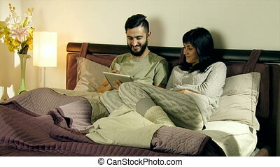Happy couple in bed playing