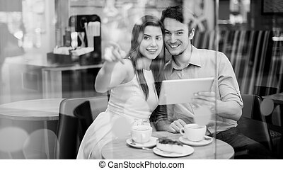 Happy couple in cafe holding digital tablet