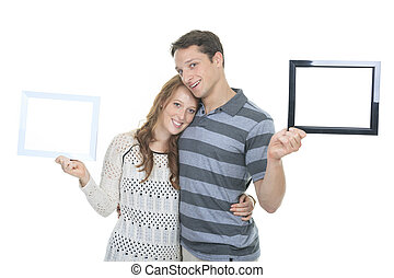 Happy couple in frame. Beautiful young couple looking through a