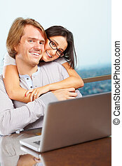 Happy couple in front of laptop - Lady hug her spouse from...