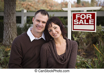Happy Couple in Front of Real Estate Sign