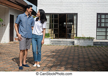 Happy couple in front of the New Home On Moving In Day, and start a new life family. Concept of homeowner and relocation