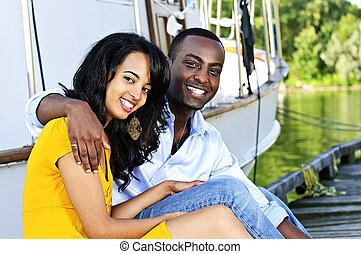 Young romantic couple sitting on dock in front of yacht