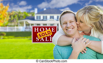 Happy Couple In Front Sold Real Estate Sign and House