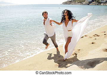 Happy couple in honeymoon on Greece, smiling and run on the beach, summer time, sunny day.