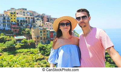 Happy couple in honeymoon with view of the old village of Five Lands, Cinque Terre national park, Liguria, Italy ,Europe