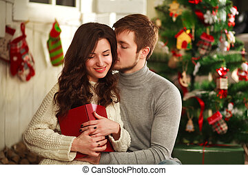 Happy couple in house on background of Christmas decorations
