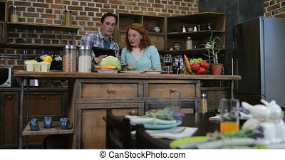 Happy Couple In Kitchen Cooking Using Digital Tablet Man And Woman Preparing Food Together At Home