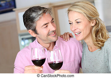 Happy couple in kitchen drinking red wine
