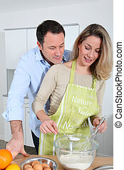 Happy couple in kitchen preparing cake