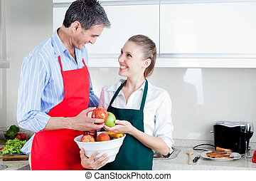 Happy Couple in Kitchen Preparing Food