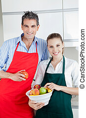 Happy Couple in Kitchen with Fruit