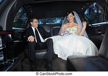 Happy couple in limousine - Newlywed in a luxury wedding...
