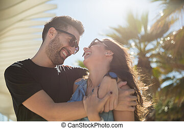 Happy couple in love cuddling together laughing