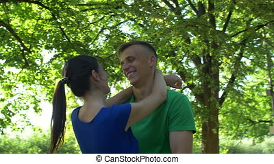 Happy couple in love embracing in public park