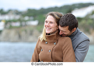 Happy couple in love flirting on the beach in winter
