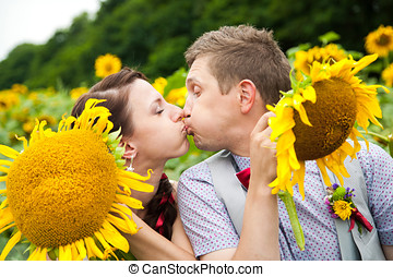 happy couple in love having fun in field full of sunflowers