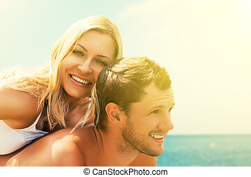 happy couple in love hugging and laughing on the beach
