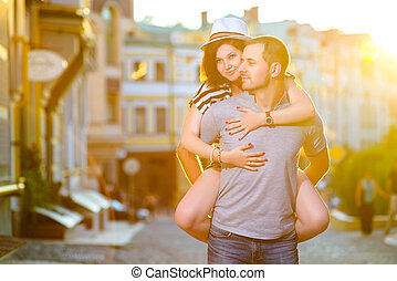 Happy couple in love hugging at city