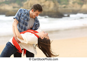 Happy couple in love joking on the beach
