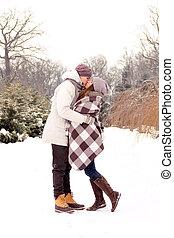 Happy couple in love kissing in park in winter