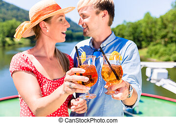 Happy couple in love on river cruise drinking coctails in summer