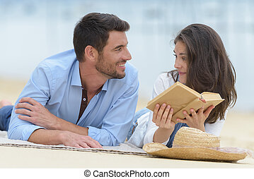 happy couple in love reading a book on the beach