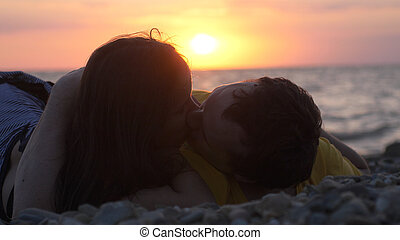 Happy couple in love romantically lay under the sun kissing together during amazing sunset