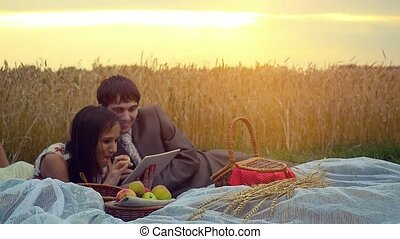 Happy couple in love sitting on picnic in wheat field use tablet and eating apples in slowmotion during beautiful sunset