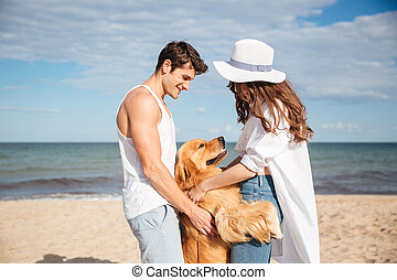 Happy couple in love sitting on the beach with dog