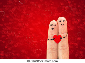 Happy couple in love with painted smiley holding red heart