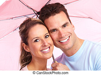 Happy couple in love under umbrella. - Happy young couple in...
