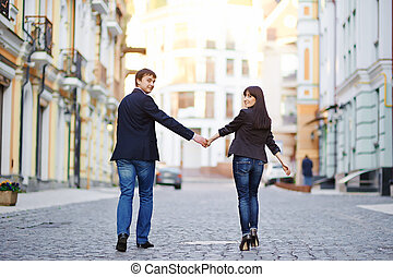 Happy couple in love walking at city