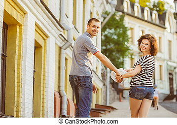 Happy couple in love walking at city. Warm toned image