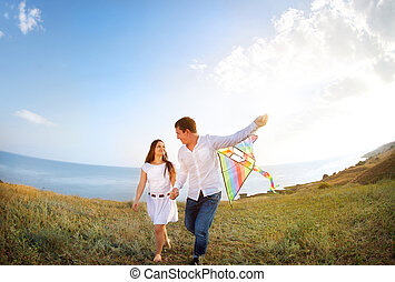Happy couple in love with flying a kite on the beach