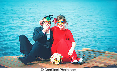Happy Couple In Masquerade Masks Against A Turquoise Lake
