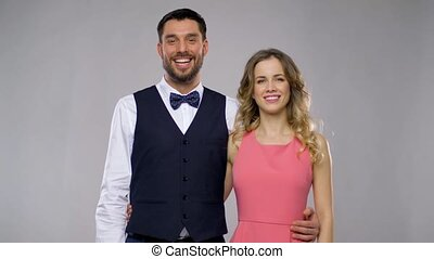 happy couple in party clothes over grey background -...