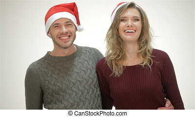 Happy couple in Santa hat laughs while standing in an embrace
