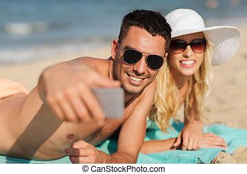 happy couple in swimwear walking on summer beach - love, ...
