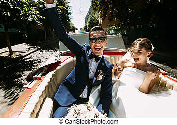 Happy couple in the car in the sunny day
