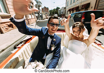 Happy couple in the car in the wedding day