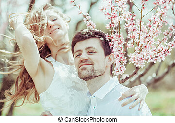 Happy couple in the park with apple tree blossom. Close-up portrait