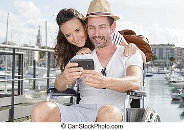 happy couple in wheelchair taking a selfie