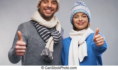 happy couple in winter clothes showing thumbs up - people,...