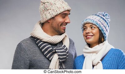 happy couple in winter wear looking at each other