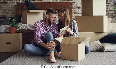 Happy couple is unpacking things after relocation opening box and looking at photos talking and laughing together. Moving to new house and relationship concept.