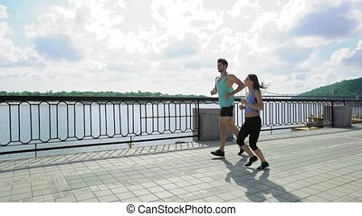 Happy couple jogging across the bridge in the city at sunny day, enjoying the view of river