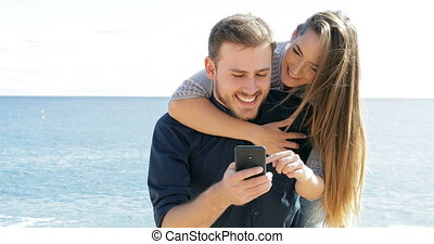 Happy couple joking and using phone on the beach - Front...