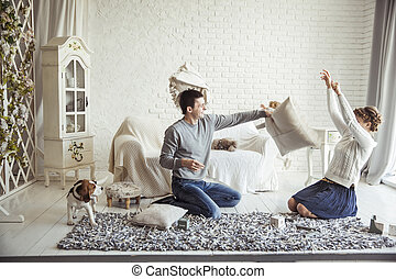 happy couple jokingly holds the pillow fight on the sofa in the living room